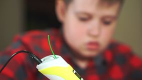 Close-up teen boy uses 3D pen. He creates a plastic 3D figure.