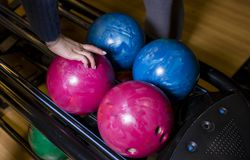 Close-up on teen children hand holding bowling ball against bowling alley - Image. Cheerful Kids are ready to play - Image. The stock image