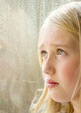 Close-up of a teen looking out a window Royalty Free Stock Images