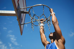 Close up of teenage boy hanging on basketball hoop Royalty Free Stock Photography