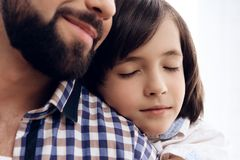 Close up. Teenage boy hugs adult father. Good relationship between father and son royalty free stock images
