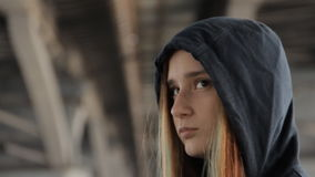 A close up of a teenage girl in a hoody with the hood on and loose multicolored hair spread in the wind under the bridge. Pillars. Water flocks visible on the stock footage