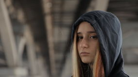 A close up of a teenage girl in a hoody with the hood on and loose multicolored hair spread in the wind under the. Unfocused bridge pillars watching the car stock video
