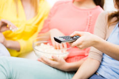 Close up of teenage girls with remote watching tv. People, television and leisure concept - close up of teenage girls with remote control watching tv and eating Royalty Free Stock Photography