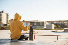 Close-up of a teenager dressed in a jeans hoodie sitting in a skate park and holding a skateboard Royalty Free Stock Images