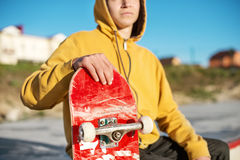 Close-up of a teenager dressed in a jeans hoodie sitting in a skate park and holding a skateboard Stock Photo