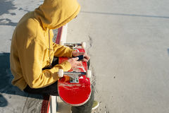 Close-up of a teenager dressed in a sweatshirt jeans and sneakers sitting in a skate park holding a phone and a Royalty Free Stock Images