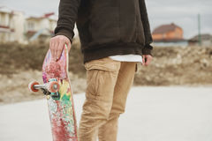 Close up Teenager standing in a right side hoodie holding a hand skateboard on the background slum Royalty Free Stock Photos