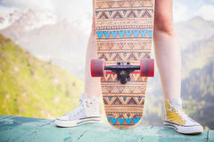 Close-up teenager standing with skateboard outdoor at mountain Stock Photography