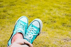 Close-up of teenager wearing green sneakers pastel on grass background stock photo