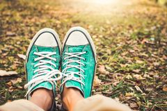 Close-up of teenager wearing old green sneakers pastel with brown foliage background stock images