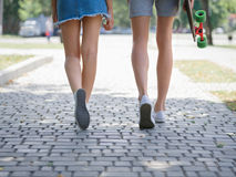 A close-up of teenages` legs in white sneakers walking in park. Young people resting after extreme funny ride on a stock photos