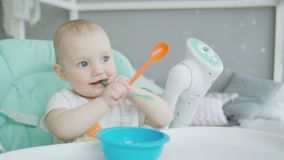 Portrait of baby sitting on highchair with spoon stock footage