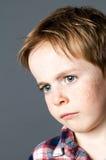 Close-up, teleurgesteld jong kind met droevige blauwe ogen en sproeten stock afbeelding