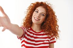 Close-up tender feminine curly redhead woman blue eyes tilting head posing striped t-shirt stretch arm towards hold. Camera smartphone taking selfie standing royalty free stock photography