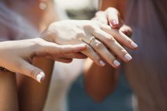 Bride`s hand with wedding ring. Close-up of tender ring on bride`s hand with white nails Royalty Free Stock Images