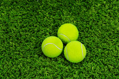 Close up of tennis ball on grass. Closeup of tennis balls on the green carpet Royalty Free Stock Images