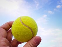 Close-up of  tennis ball in a man  hand agains blue sky stock images