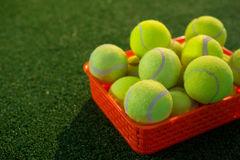 Close up of tennis balls in orange container Royalty Free Stock Photo
