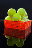 Close up of tennis balls in red plastic basket with reflection. Against black background Stock Photo