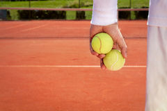 Close up of tennis balls in sportsman hand Stock Image