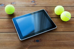 Close up of tennis balls and tablet pc on wood Royalty Free Stock Photography