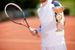 Close up of tennis goblet. In winner`s hand Royalty Free Stock Images