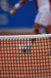 Close-up of a tennis net. A close-up of a tennis net on a clay tennis court. There is a tennis player that is blurred in the background Stock Photos