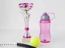 Close up of tennis racket, ball, cup and bottle Royalty Free Stock Images