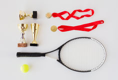 Close up of tennis racket, ball, cups and medals Royalty Free Stock Photography