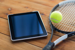 Close up of tennis racket with ball and tablet pc Royalty Free Stock Image