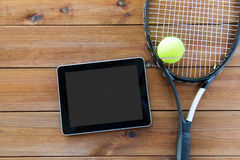 Close up of tennis racket with ball and tablet pc Royalty Free Stock Images