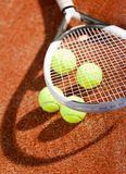 Close up of tennis racket and balls. On the clay tennis court Royalty Free Stock Photography