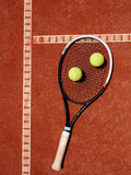 Close up of tennis racket and yellow balls at red clay Stock Photography
