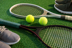 Close up of tennis rackets with balls and sports shoes Stock Photography