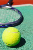 Close up of tennis racquet and ball. On the clay tennis court Royalty Free Stock Photography