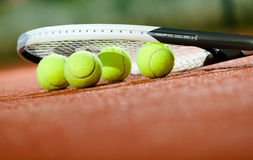 Close up of tennis racquet and balls. On the clay tennis court Royalty Free Stock Images