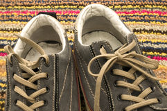 Close Up of Tennis Shoes. Against Multi Colored Rug Stock Photo