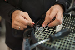 Close up of tennis stringer hands doing racket stringing. Stringing Machine. Close up of tennis stringer hands doing racket stringing in his workshop Stock Image