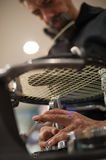 Close up of tennis stringer hands doing racket stringing. Stringing Machine. Close up of tennis stringer hands doing racket stringing in his workshop Stock Photo