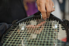 Close up of tennis stringer hands doing racket stringing. Stringing Machine. Close up of tennis stringer hands doing racket stringing in his workshop Royalty Free Stock Image