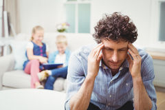 Close-up of tensed man while children in background Stock Photo