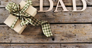 Text dad with gift box. Close-up of text dad with gift box on wooden plank stock video