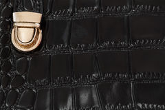 Close-up texture of black handbag from genuine leather with embossed under the skin of reptile, gold lock. Concept of Stock Images