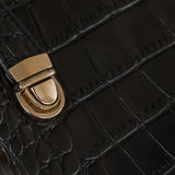 Close-up texture of black handbag from genuine leather with embossed under the skin of reptile, gold lock. With place. Close-up texture of black handbag from Stock Photos