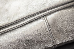 Close-up texture of evening silver handbag, clutch from genuine leather. Concept of shopping, manufacturing, lifestyle. Close-up texture of evening silver Royalty Free Stock Photography