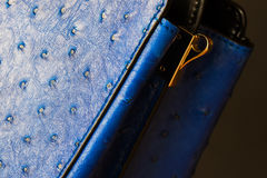 Close-up texture of fashion blue color handbag from genuine leather, embossed under skin Ostrich, gold detal for strap Royalty Free Stock Images