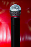 Close up texture of microphone in music hall against red luxury Stock Photography