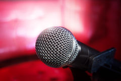 Close up texture of microphone in music hall against red luxury Royalty Free Stock Image