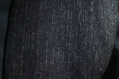 Close up texture of navy blue fabric blanket or throw. Black,grey and white vertical flecks stock photos